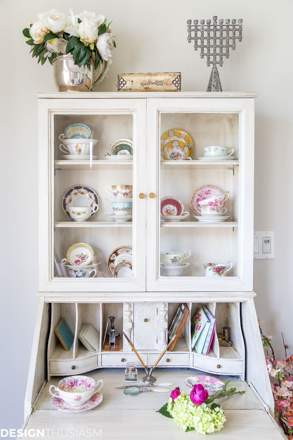 vintage teacups and saucers displayed in an antique cabinet