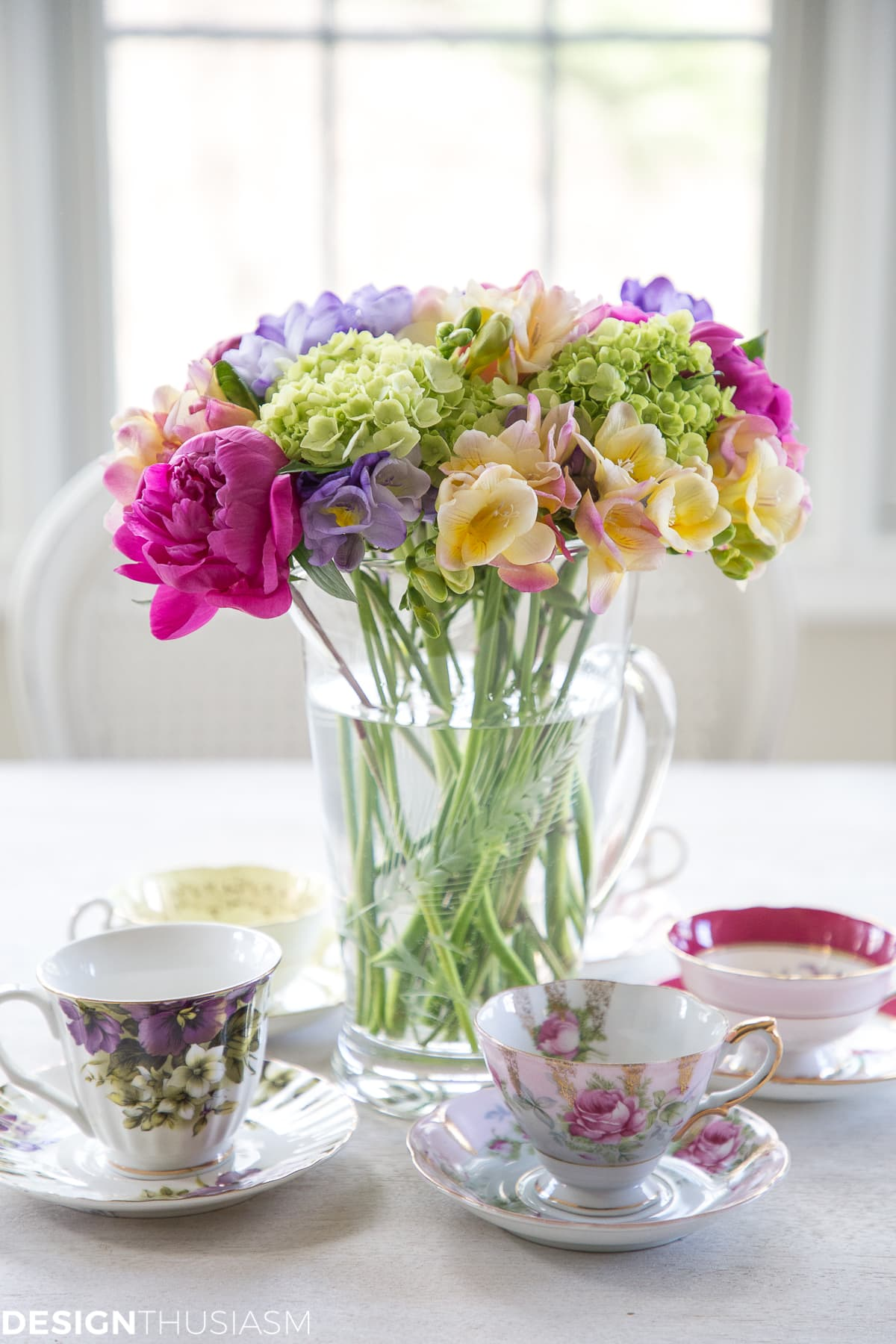vintage teacups and saucers around a floral centerpiece
