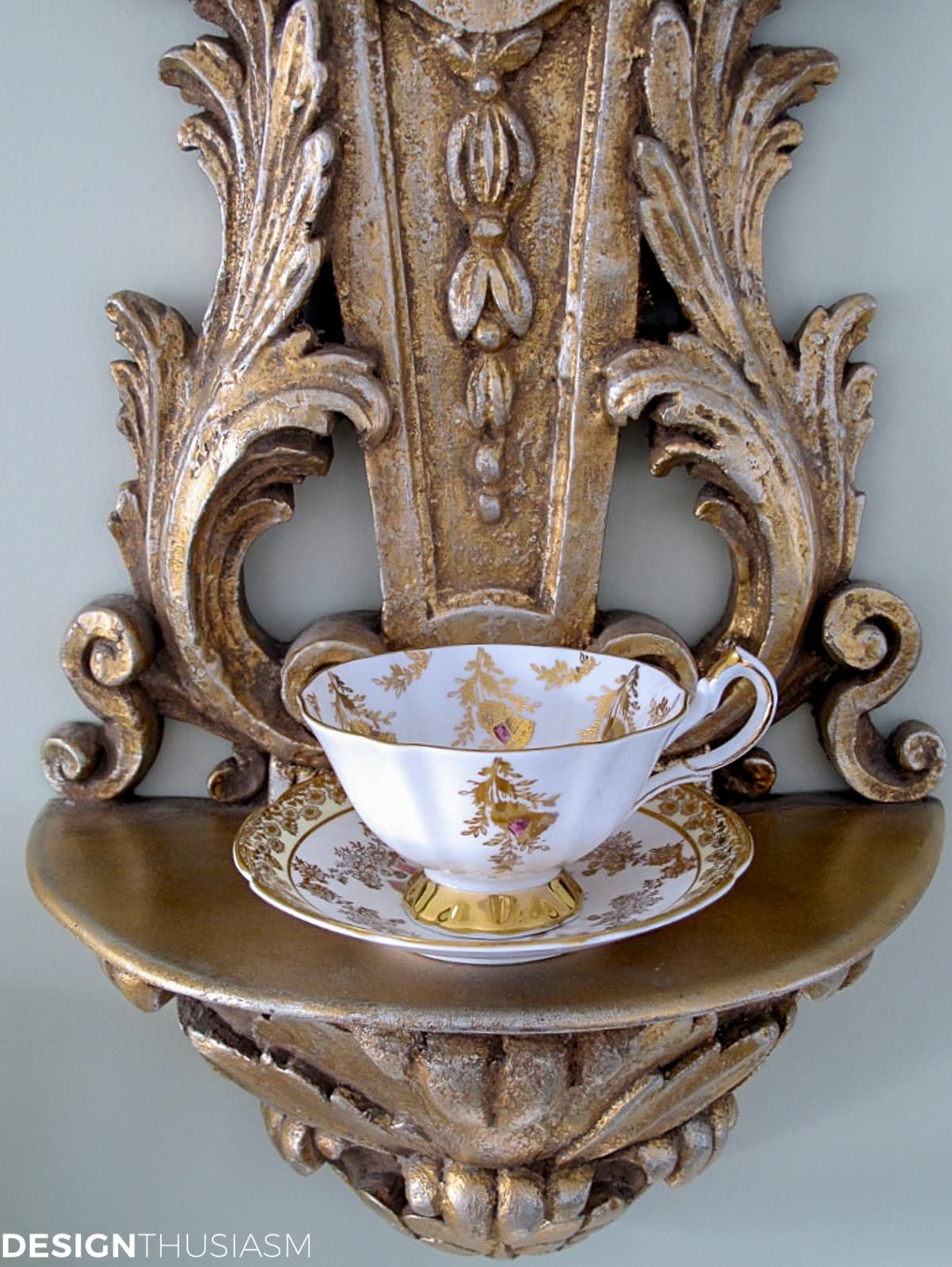 vintage teacup and saucer displayed on a shelf sconce