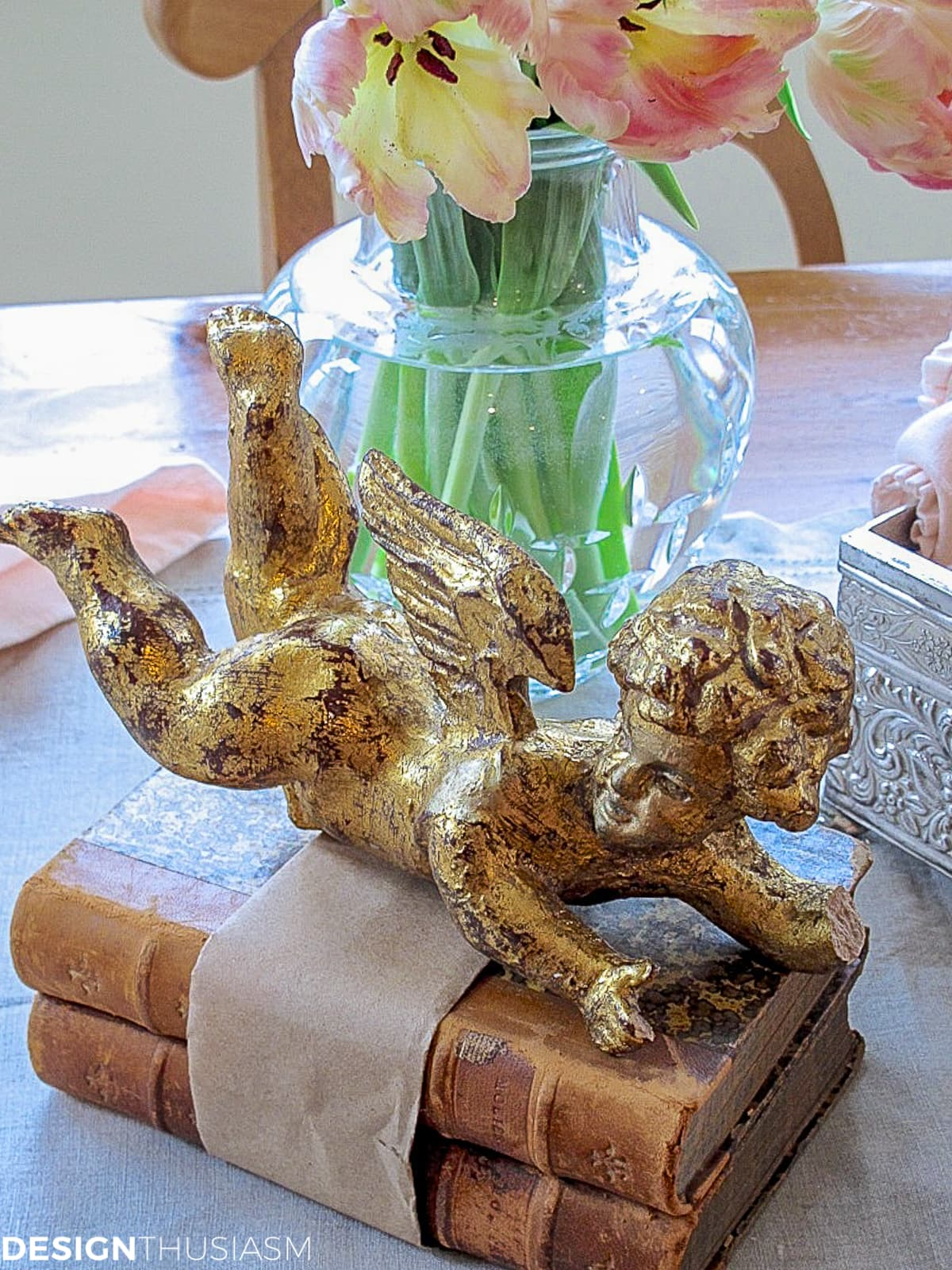 gilded cherub on vintage books on a kitchen table