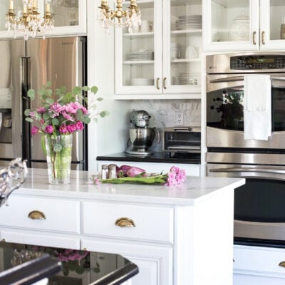 white kitchen with painted glass front cabinets