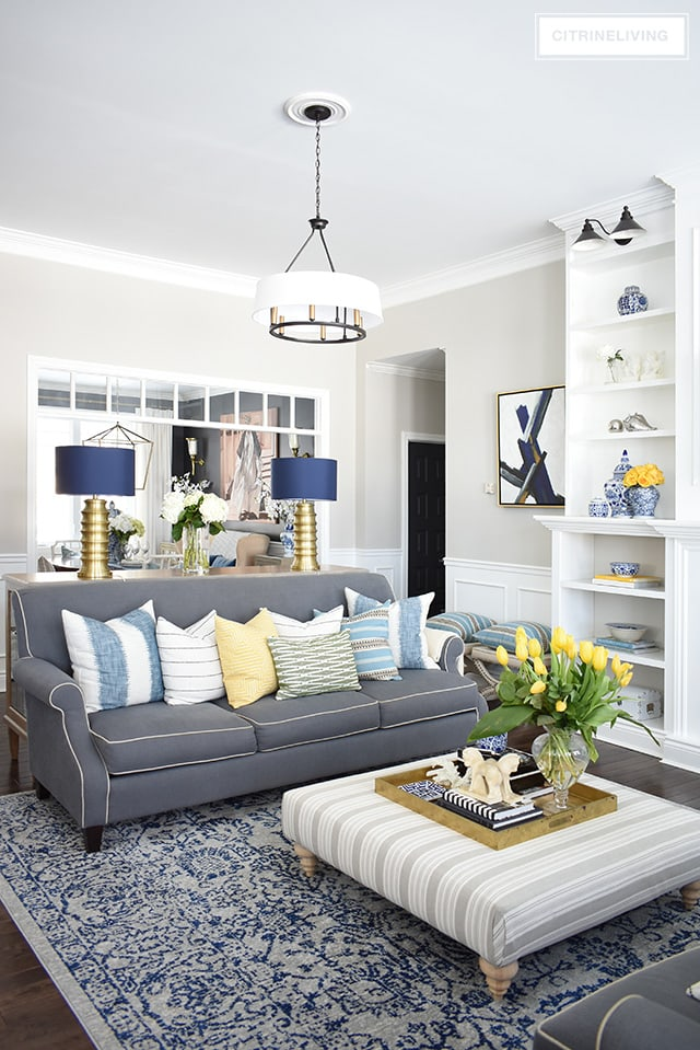living-room-with-blue-and-grey-rug-grey-sofa-blue-white-yellow-spring-decor