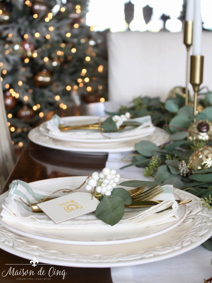 White plates with eucalyptus leaves and white berries on it.