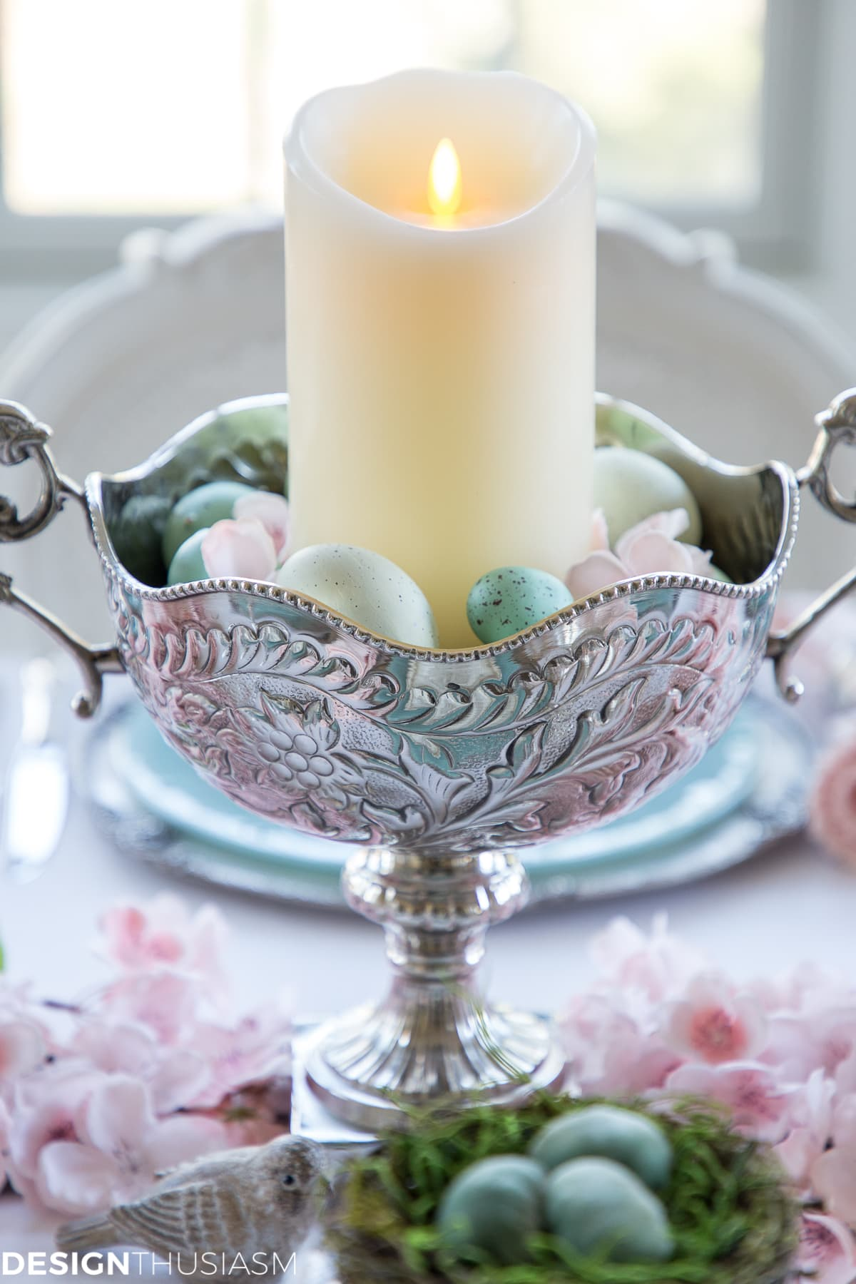 Easter centerpiece in a spring tablescape with eggs and cherry blossoms
