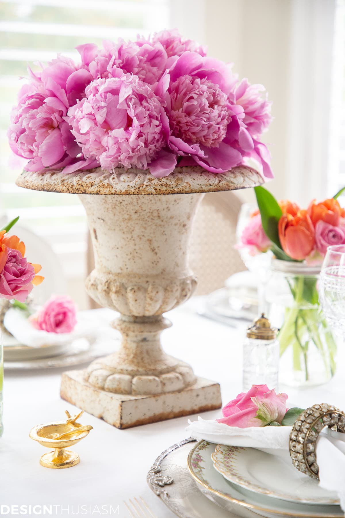 white dining table setting with a peony centerpiece