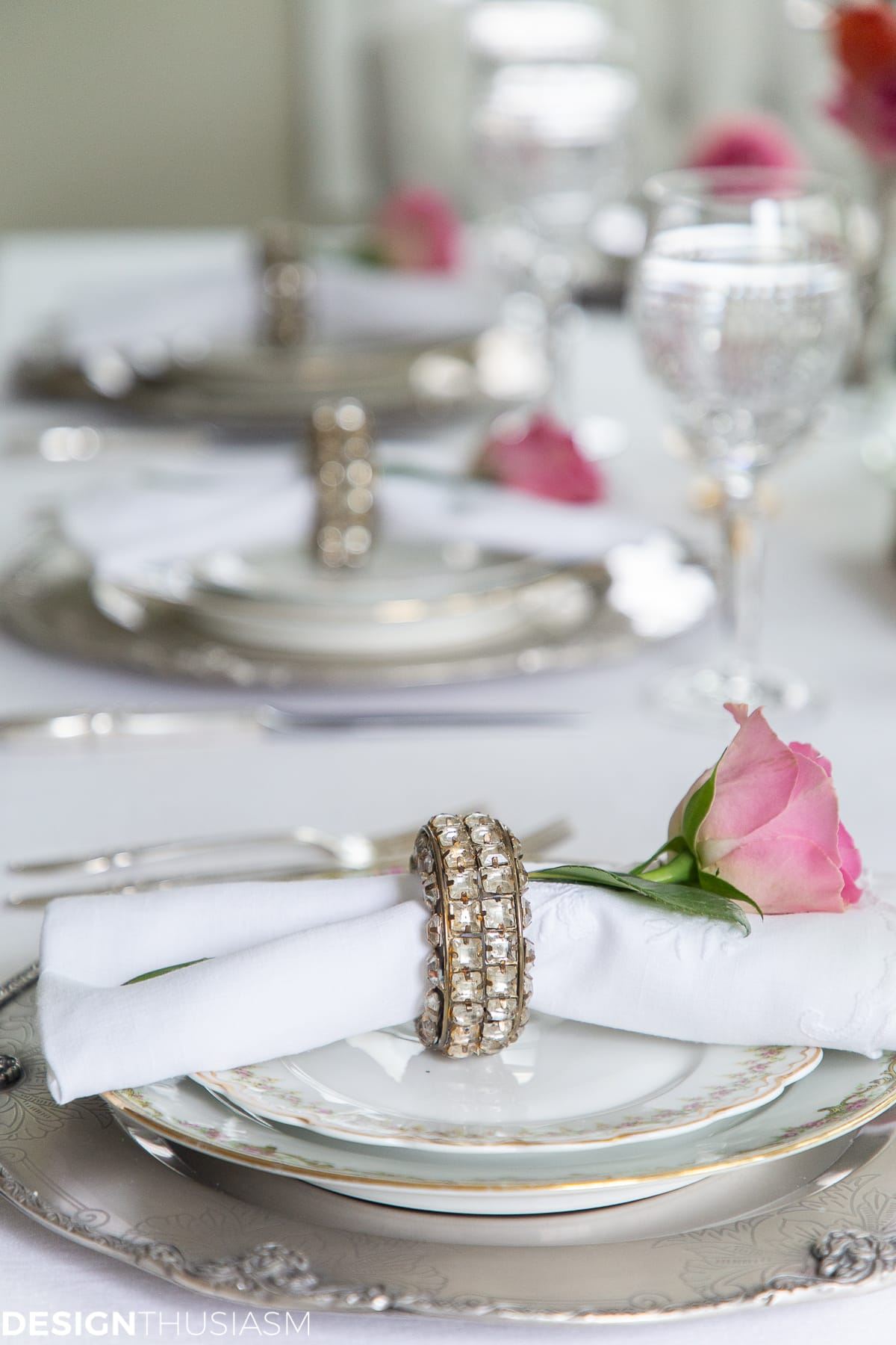 white dining table setting with rose napkin rings