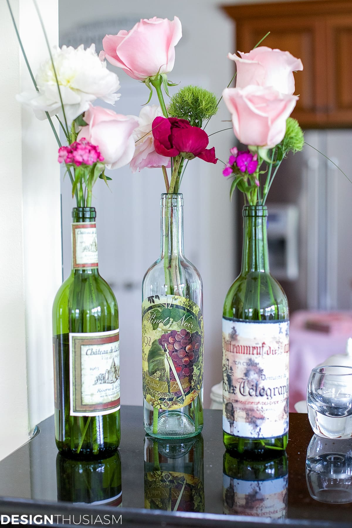 pink flowers in wine bottles