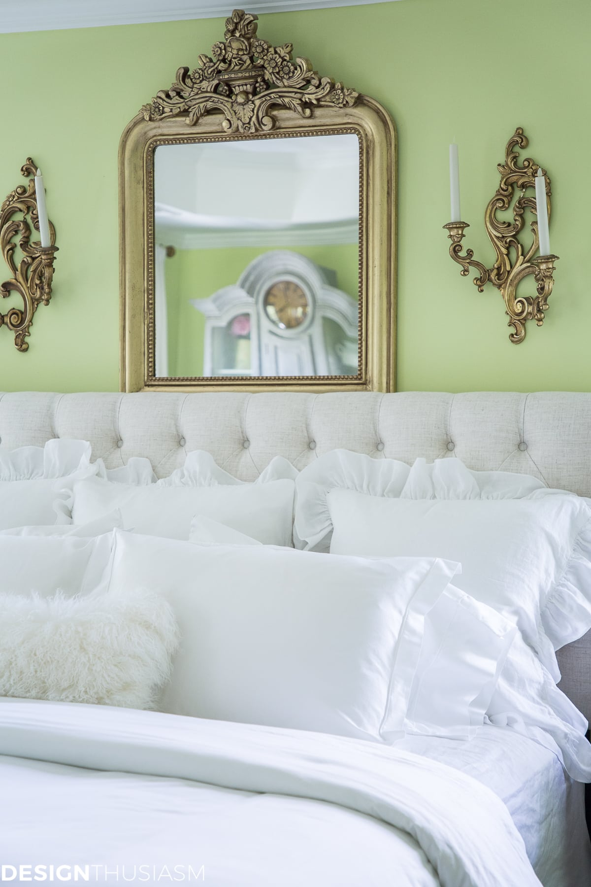 luxury white bedding with gilded mirror and sconces