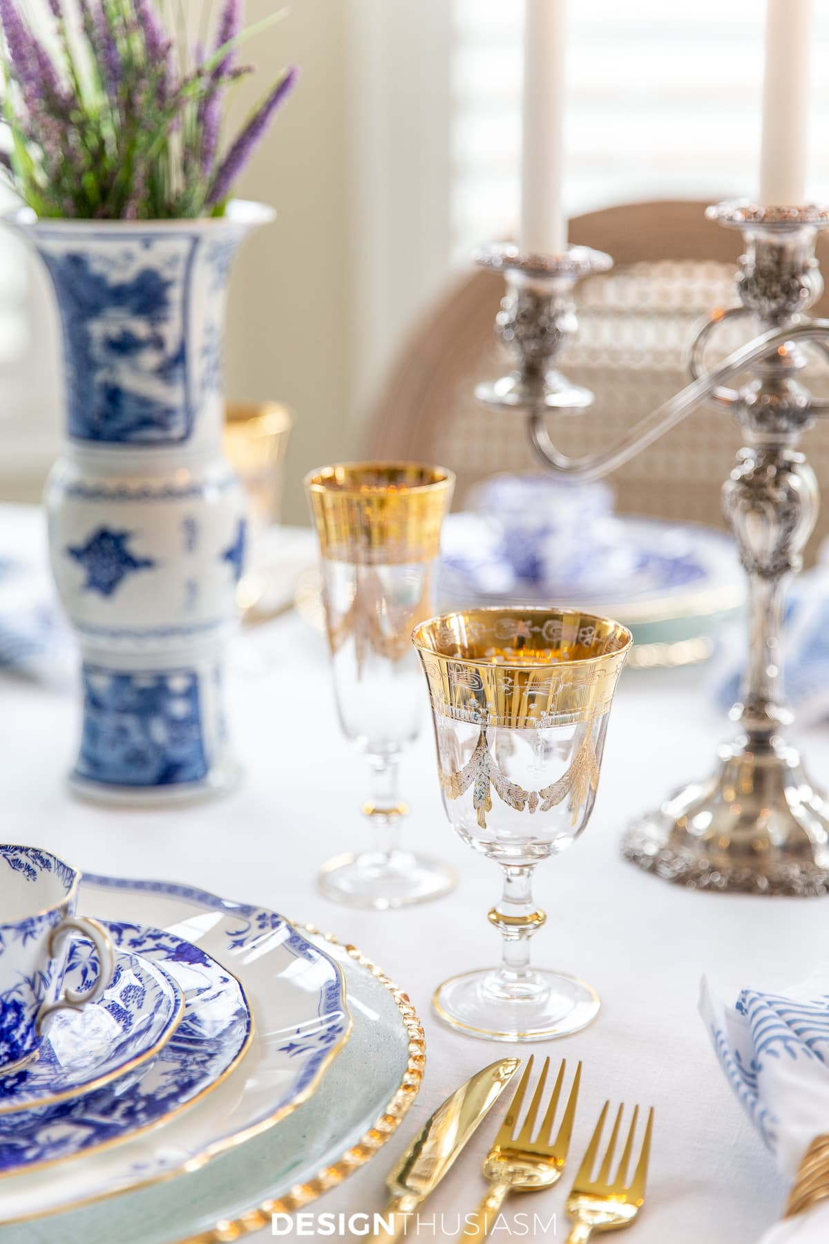 blue and white china table setting with gold rimmed goblets